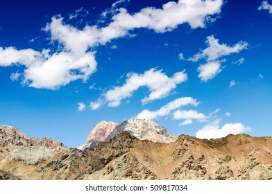 mountain peaks against the blue sky with clouds