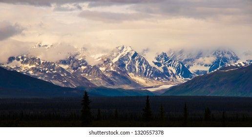 Mountain peaks in Alaska on the Denali Highway jut into the sky