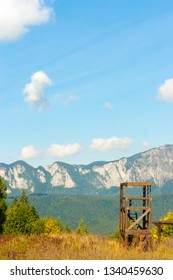 Mountain peaks in bright sunlight. Wooden construction for training on a meadow.