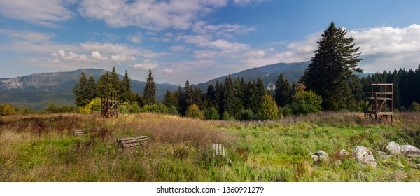Mountain peaks in bright sunlight. Wooden constructions for training on a meadow.