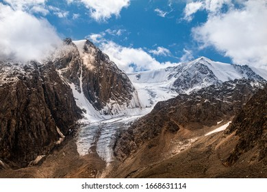 Mountain peaks covered with snow and glacier. Dark rocks on a background of light snow and ice. Mountain Altai nature on a bright day with blue sky and white clouds over the mountains. Siberia, Russia