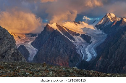 Mountain peaks in the light of the rising sun. Rocky relief, severe weather.
