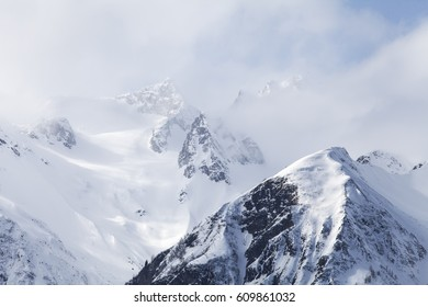 Mountain peaks near Haines Alaska with fog and blue sky in winter.