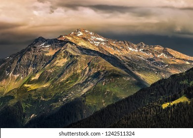 Mountain peaks of the valley Prättigau in the Canton Graubünden of Switzerland. Dark clouds over mountain peak. Lights and Shadows game on the mountain peak itself.