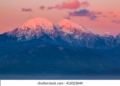 Mountain peeks of Kocna and Grintavec in Kamnik-Savinja Alps just before the sunset, with the afterglow lit sky viewed from Kranj, Slovenia