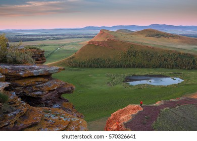 """Mountain range """"Chests"""" during a colorful sunrise in the Republic of Khakassia, Russia. People admires the sunrise"""