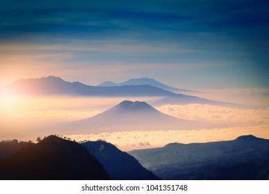 Mountain range in fog with sunlight.