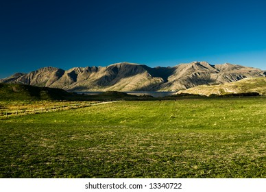Mountain range with green meadow near Wanaka, New Zealand.