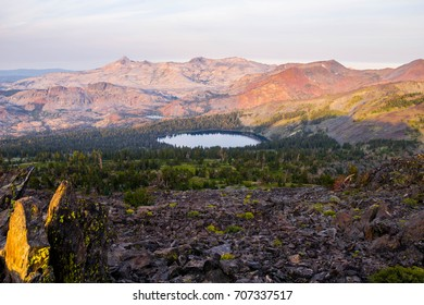 A mountain range and a large pond while looking South from the top of Mount Tallac in Lake Tahoe, California.