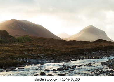 Mountain range near the famous Sligachan bridge on an early autumn morning at sunrise and a little stream as foreground (Isle of Skye, Scotland, Europe)