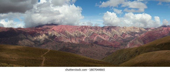 Mountain range. Panorama view of the footpath in the yellow grassland leading to the colorful Hornocal mountain under a dramatic cloudy sky.
