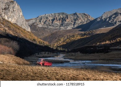 Mountain range surrounded by pine forest with red motobike and river at the background in clear blue sky day in autumn season at Yading National Park, Daocheng, Sichuan, China