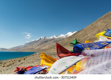 Mountain range view at Pangong Lake.Prayer flags blow in the wind blur on foregroud.