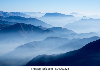 Mountain range with visible silhouettes through the morning blue fog.