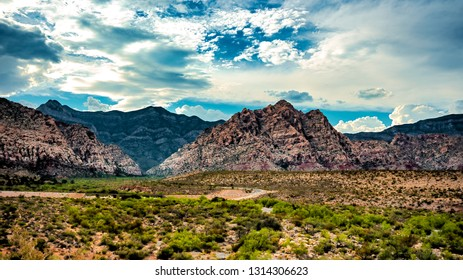mountain ranges across the desert way and clouds lingering above at Red Rock Canyon, Las Vegas, Nevada, United States.