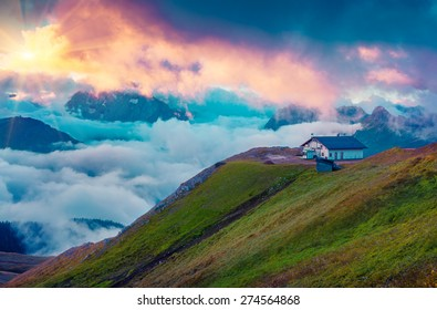 Mountain refuge in the foggy Val di Fassa valley with passo Sella at early morning. National Park. Dolomites, South Tyrol. Location Canazei, Campitello, Mazzin. Italy, Europe.