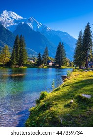 The mountain resort of Chamonix, Haute-Savoie. City Park is illuminated by sunset. The lake reflected the snow-capped Alps and evergreen spruce