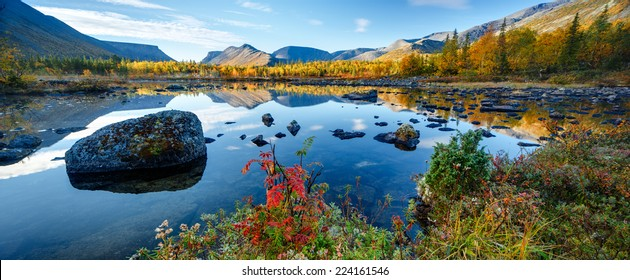 Mountain ridge panorama reflected in shallow Polygonal freshwater lake with bright autumn foliage in foreground, Hibiny mountains above the Arctic Circle, Russia