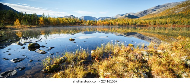 Mountain ridge panorama reflected in shallow Polygonal freshwater lake with bog hummocks in foreground, Hibiny mountains above the Arctic Circle, Russia