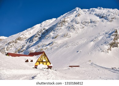 Mountain ridge with snow on a beautiful winter day with sunshine. sunny winter landscape on the Transfagarasan, with the road blocked by the avalanche. Mountain refuge Lake Balea. Fagaras Mountains.