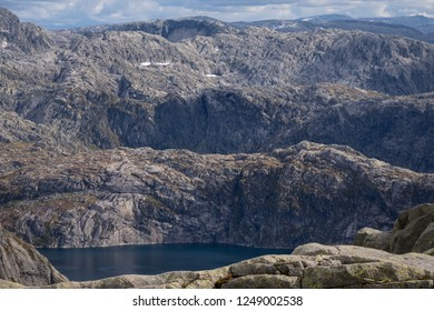 Mountain ridges near the glacier, bare stones without vegetation. Ridges separated by deep, dark glacial troughs (valleys). Lake in the nearest valley. Norway.
