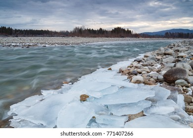 The mountain river is covered with ice at the beginning of winter.