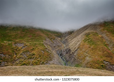 Mountain river flowing on green hill