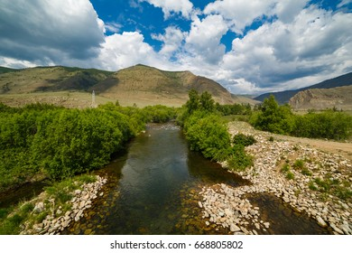 Mountain river in the gorge on a sunny day with large white clouds