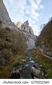 Mountain river landscape in Romania with high peaks and blue sky