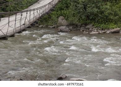 Mountain river and pedestrian bridge through it