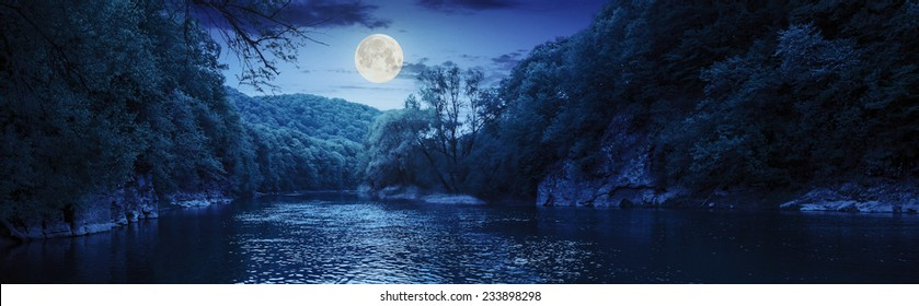 mountain river with stones on the shore in the forest near the mountain slope at night in full moon light