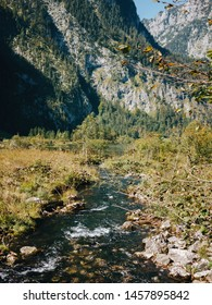 Mountain river stream against forested mountains during sunny autumn day, Berchtesgadener Land, Bavaria, Germany