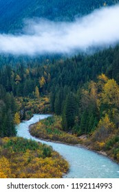 A mountain river surrounded by colorful autumn trees and low clouds, British Columbia, Canada
