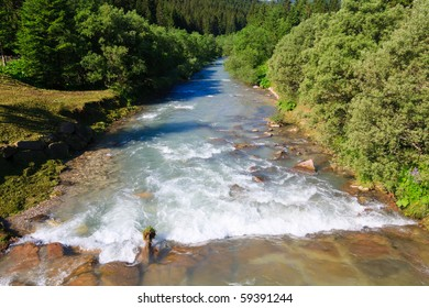 Mountain river that flows through green valley in Dolomites.