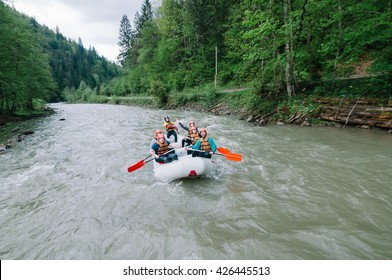 Mountain river, Ukraine - May 7, 2016.Group of men and women doing white water rafting activity at mountain river, Ukraine on May 7, 2016.