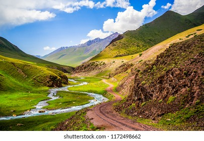 Mountain river valley road landscape. Mountain road at mountain river stream in mountain valley panorama