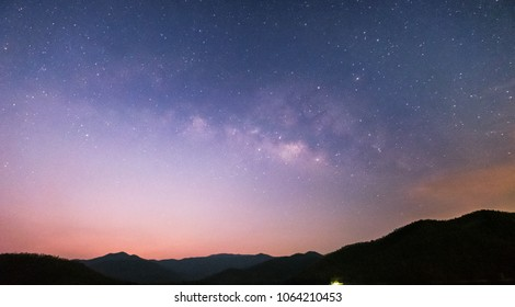 Mountain and river views at night The Milky Way and the Stars shine in the dark. - Shutterstock ID 1064210453