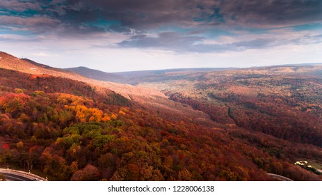"Mountain road and autumn trees in GUAM gorge ""Guamka"", North Caucasus, Russia. Yellow, red and green nature, top view. Aerial drone shoot with wonderful sky and clouds."