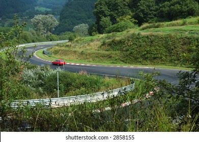 mountain road with a car in the forest
