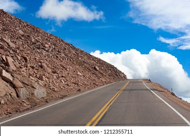 A mountain road climbs towards the clouds.