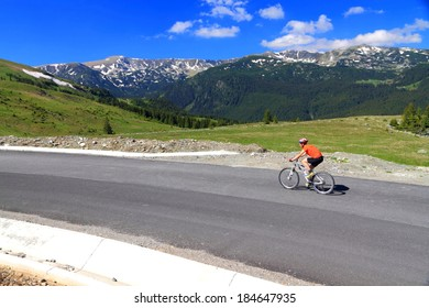 Mountain road and cyclist woman ascending in fine summer day