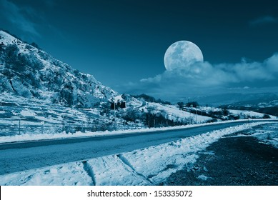 mountain road in the evening with moon in the sky