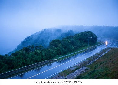 Mountain road in foggy dusk, motorcycle riding on asphalt road through the mountain top of Phnom Bokor Mountain in rainy day, Preah Monivong Bokor, Kampot, Cambodia. Shallow dept of field. Blue tone.