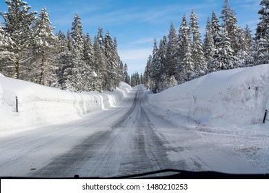 Mountain road highway 88 towards Carson Pass, California, USA, on a winters day featuring five feet of snow on the side of the road after several storms, a sign of dangerous driving conditions