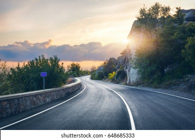 Mountain road. Landscape with rocks, sunny sky with clouds and beautiful asphalt road in the evening in summer. Vintage toning. Travel background. Highway in mountains. Transportation - Shutterstock ID 648685333