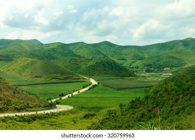 Mountain road in North Korea. Mountains covered with green vegetation.
