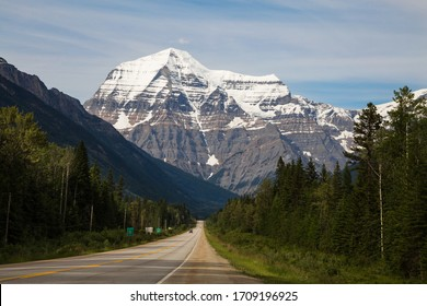 Mountain road passing through evergreen forests below the towering snow covered peak of below Mount Robson, British Columbia, Canada on a hazy day in a picturesque landscape