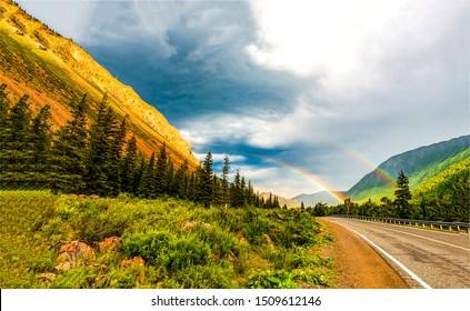 Mountain road rainbow landscape. Rainbow mountain road view. Mountain road rainbow scene. Mountain road rainbow