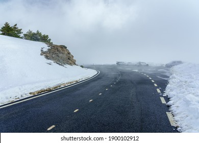 Mountain road with snow and fog on sunny day.