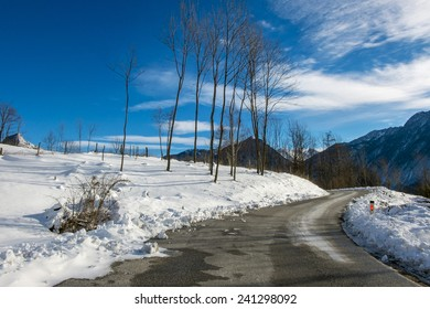 mountain road with snow under a blue sky